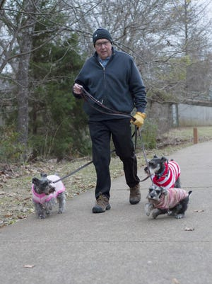 Stephen Bishop of Tyler takes three sweater-wearing dogs on a walk at the Rose Rudman Trail in Tyler, Texas on Friday, Dec. 29, 2017. The temperatures are expected to drop in East Texas going into the New Year with possible lows in the 20s on New Year's Eve.