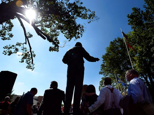 People gather around the Clarence Darrow statue for photographs after the dedication ceremony in front of the Rhea County Courthouse, Friday, July 14, 2017, in Dayton, Tenn. Darrow was the lawyer who defended John T. Scopes, a biology teacher, who fought Tennessee's law banning the teaching of evolution. (AP Photo/Mark Zaleski)