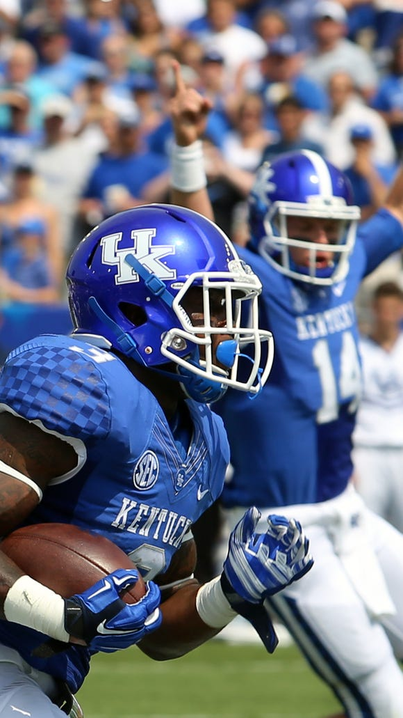 Kentucky's JoJo Kemp scores the first touchdown of the season for the Cats as teammate Patrick Towles celebrates in the background.  Aug. 30, 2014
