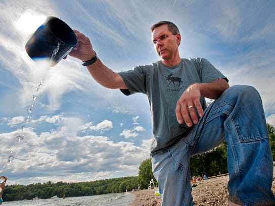 James Ehlers pours a cupful of lake water at North