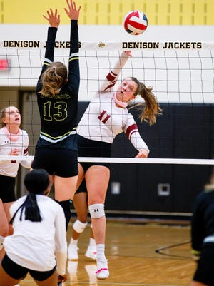 Sherman's Ryan Dobbs attacks at the net while Denison's Katherine Hodge attempts to block during District 10-5A action at Denison. Sherman came away with the victory.