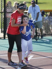 Lilly Ecklund, right, gets help going to first from