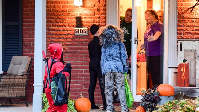 Trick-or-treaters take turns telling jokes on Sunday, Oct. 30, 2016, on Beggars' Night in Urbandale.