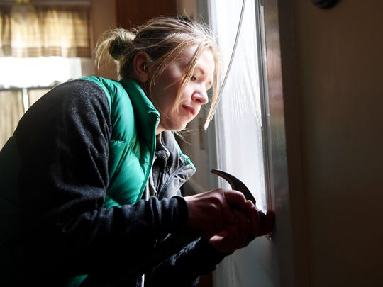 Yulia Shaffer, Energy Savers Network Volunteer Coordinator, installs an interior storm window kit at a Blue Horizons Project home in Kenilworth March 21, 2018.