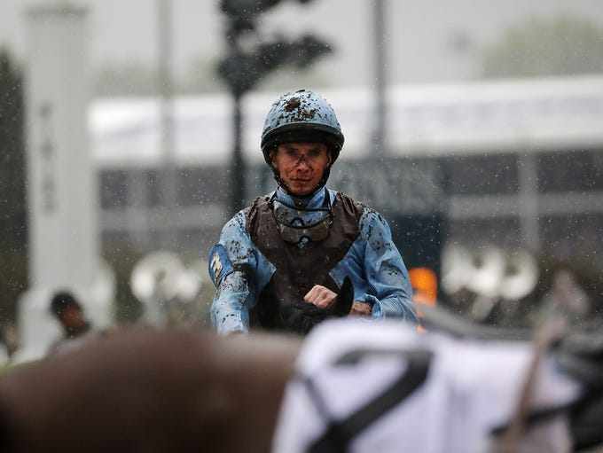 Covered in mud, jockeys head back for their next race