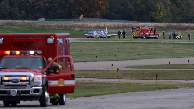 Firefighters and Ohio Highway Patrol troopers respond to an airplane that landed without front landing gear Saturday at the Fairfield County Airport in Lancaster. No one was injured.