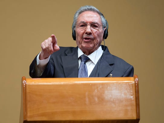 Cuban President Raul Castro points to a member of the