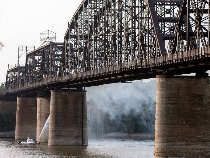 Members of the Louisville Fire & Rescue Marine Unit sprayed water from below in an effort to extinguish the fire on the Kentucky & Indiana Terminal Bridge on Monday evening.