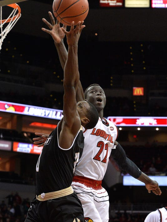 Louisville forward Deng Adel (22) attempts to block the shot of Bryant guard Ikenna Ndugba (0) during the first half of an NCAA college basketball game, Monday, Dec. 11, 2017, in Louisville, Ky. (AP Photo/Timothy D. Easley)