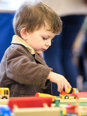 Noah Fakih, 2 years-old, plays with a wooden train set as he visits the Local Loco Model Railroad Club show held at the library Saturday and Sunday, January 15, 2017.