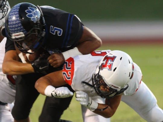 At left, Cathedral City High School's Jordan Wallace is stopped for a loss of yardage by Heritage High School's Javier Luna during Cathedral City's lost at home.