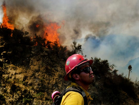 A firefighter watches as the Cranston fire grows to more 1,200 acres in the San Bernardino National Forest above Hemet, Calif., Wednesday, July 25, 2018. The San Bernardino National Forest borders the town of Idyllwild and Cal Fire, USFS and the local fire department leverage collective resources to fire fires in the region.