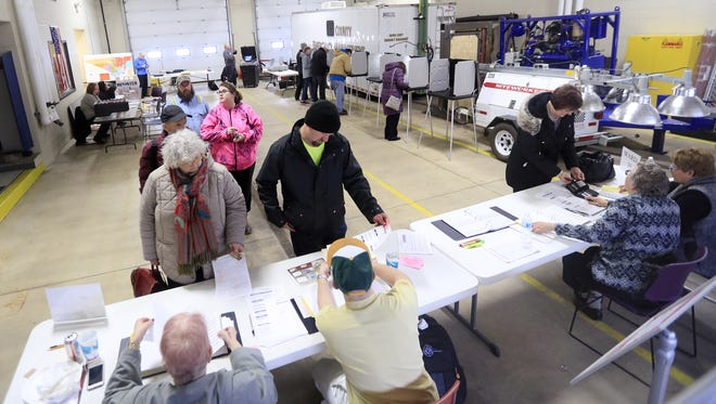 Voters line up to fill out their ballots at Fire Station No. 2 in Howard on Tuesday.