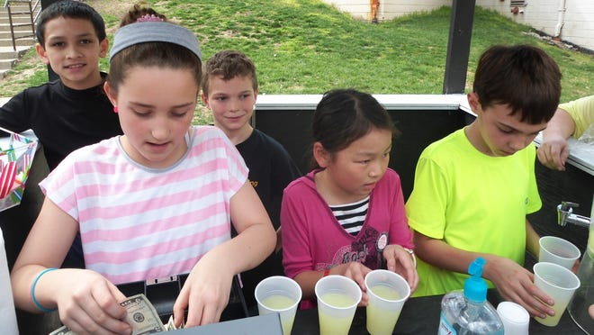 Jolie Brausch makes change, Julianne Lin hands out the lemonade, and Sam Cline pours it while Josiah Soberano and Seamus Taylor hand take orders for the popsicles during a busy Friday afternoon at the St. Columban School lemonade stand. All profits go to PowerUp Ethiopia to build solar wells for clean water in Ethiopia.