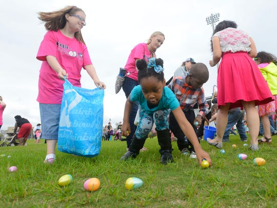 Kids race around snatching up Easter eggs during the
