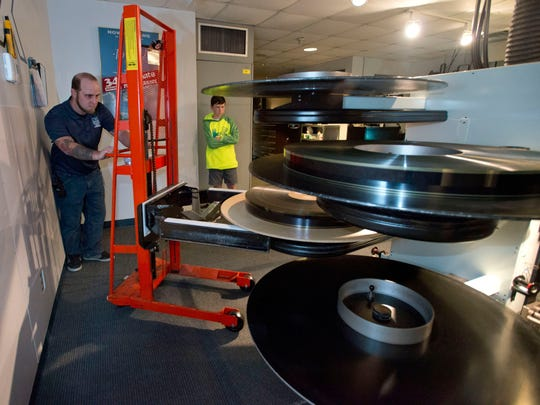 "Mike Moodispaugh, loads one of the last ""films"" onto the IMAX projector at the National Naval Aviation Museum Thursday Dec. 31, 2015, while Carson Crabtree, right,  looks on.  On Jan. 1st the museum will stop showing ""film"" movies and convert to a new digital projection system. The process is expected to be complete in March 2016."