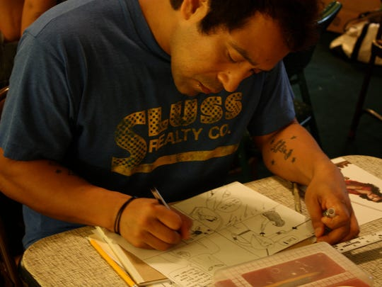 Aurelio Villa Luna Diaz works on a comic book during the 2013 24-Hour Comic Day challenge.