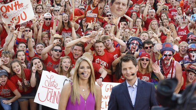 """""""SportsCenter on the Road"""" hosts Sara Walsh and Matt Barrie are surrounded by St. John's fans while filming an ESPN promo at Clemens Stadium in Collegeville the night before a live broadcast highlighting the St. John's/St. Thomas rivalry on Sept. 26."""