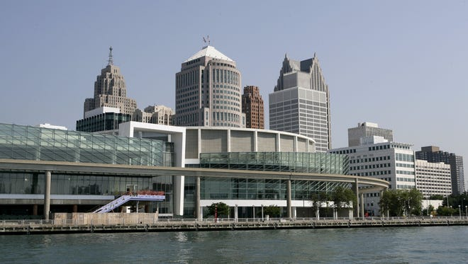 Cobo Center, the foreground building with the glass, is on the Detroit River with the skyline of Detoit in the background.