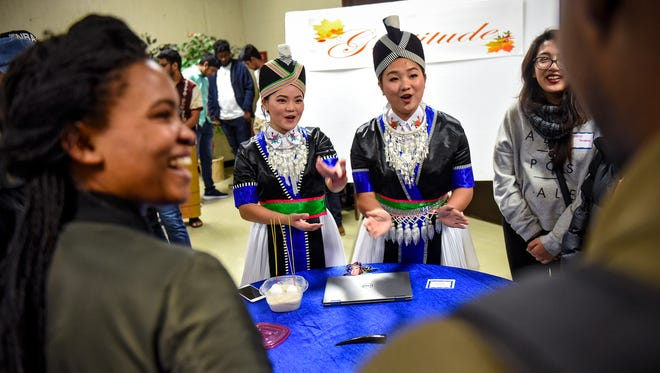 Pader Thao and Chao Her share Hmong religious customs during an International Service for Peace and Thanksgiving Tuesday, Nov. 21, at the Newman Center in St. Cloud.