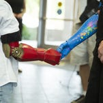 Twelve children around the country will receive 3-D printed, bionic arms like the ones pictured in time for Christmas.