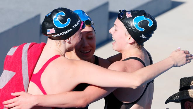 FILE -- Claire Adams (R) celebrates after winning in the women's 100-meter backstroke final during the Phillips 66 National Championships at Northside Swim Center.