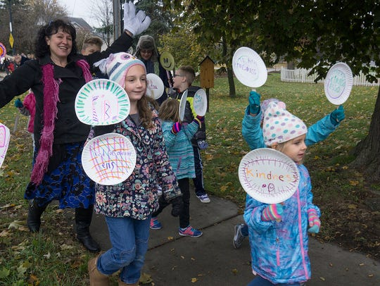 Children, teachers and parents march along Haggerty Road to Five Mile on World Kindness Day.