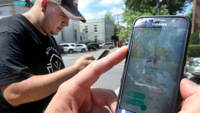 Chaz Fritschow catches a Rattata Pokemon while playing the Pokemon GO game in downtown Murfreesboro as his friend Josh Chambliss, left, also plays the mobile Pokemon GO game, on Monday July 11, 2016.