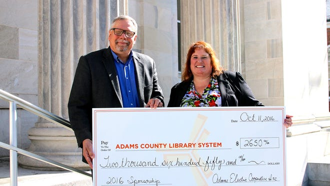 Duane Kanagy, manager of Communications/Community Services for Adams Electric Cooperative Inc., left, presents a check for $2,650 to Karla Trout, executive director of the Adams County Library System.