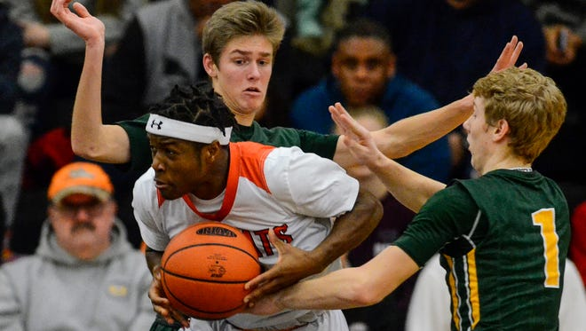 Northeastern's Fred Mulbah is fouled by York Catholic's Robbie McNamara (1) during the York-Adams semifinal game, Wednesday, Feb. 15, 2017. The Bobcats defeated the Fighting Irish, 69-66, to advance to Friday night's championship game against Central York. John A. Pavoncello photo