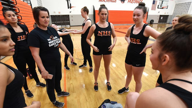 Dance team coach Sarah Benish, left, talks to her squad before dancers start going through a routine on April 11.