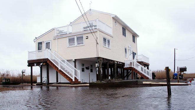 This March 14, 2017, photo shows Jim and Maryann O'Neill's home in a back bay neighborhood of Manahawkin N.J., surrounded by water after a moderate storm. He lives in a low-lying area near the Jersey shore, and is often affected by back bay flooding. As sea levels rise, thousands could leave the coast and move inland.