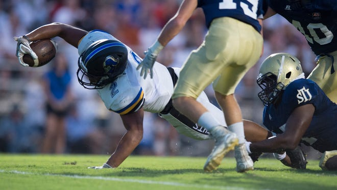 Catholic's Tyler Price (2) is tackled by St. James' Blake Underwood during a game between St. James and Catholic Friday, Sept. 2, 2016, in Montgomery, Ala.