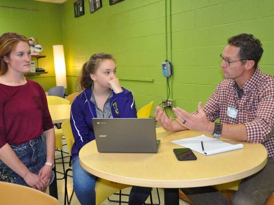 Mark Gustin (right) with Hannah Brandenstein (left) and Brianna Beers (middle) in the OHS Personal Finance Class. Gustin is mentoring Brandenstein and Beers on a savings plan they created for their class work.