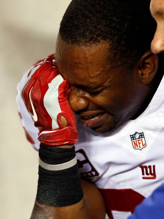 New York Giants' Victor Cruz covers his face after getting injured and carted off the field in the third-quarter of the NRL football game  against the Phildelphia Eagles on Sunday, Oct. 12, 2014 at Lincoln Financial Field in Philadelphia.  (AP Photo/Philadelphia Inquirer, Ron Cortes)