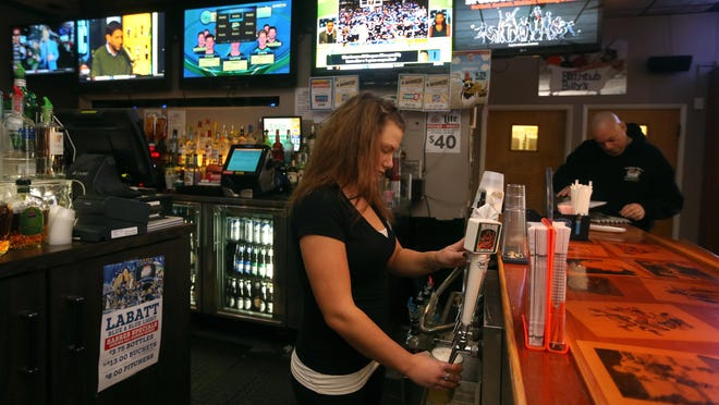 Jessica Niell pours a beer behind the bar at Bathtub Billy's.