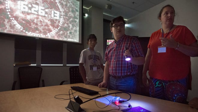 Teacher/group leader, Kala Jo Grice-Dobbins, right, helps students, Peter Tubia, center, Caleb Tamberella, solve clues a timed puzzle using newly learned computer coding skills during the GenCyber Camp at University of West Florida on Tuesday, July 10, 2018.