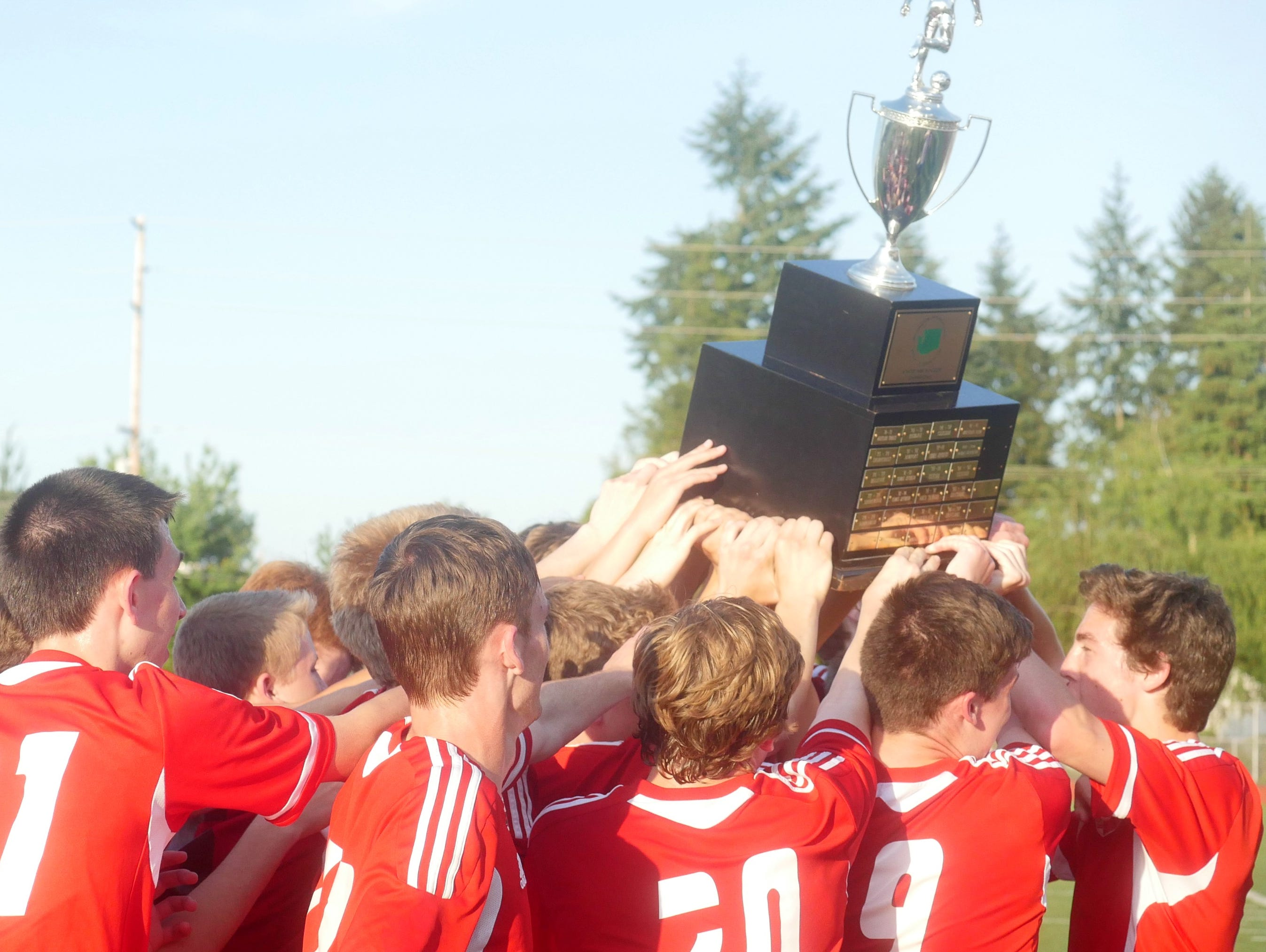 The Snohomish team lifts up its 4A boys soccer championship trophy.