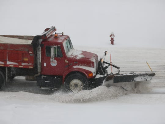 Crews from Port Clinton's street department work to keep the city roads clean from snow during a winter storm.