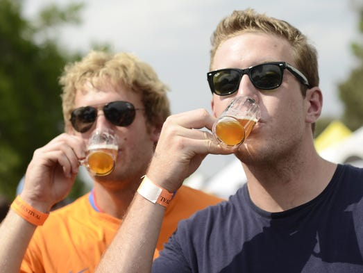 Danny Christopher, right, and Sean Wellfare takes swigs of beer during the second day of the Colorado Brewers' Festival in 2012.