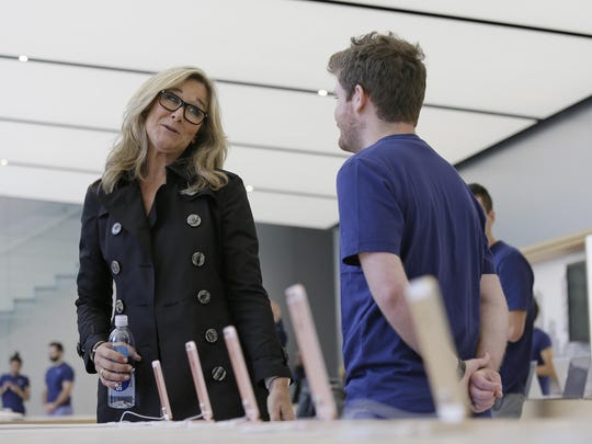 Angela Ahrendts, left, Apple's senior vice president of retail and online stores, speaks with an employee during a preview of the new Apple Union Square store.