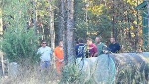 In handcuffs and an orange jumpsuit, Todd Kohlhepp accompanies law-enforcement officers on the property he owns in Woodruff on Nov. 5. Investigators have said he directed them to three bodies buried there.