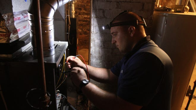 Michael Petrella, a field technician with John Betlem Heating & Cooling, checks a switch inside a furnace during an annual service cleaning, inspection and tune-up.