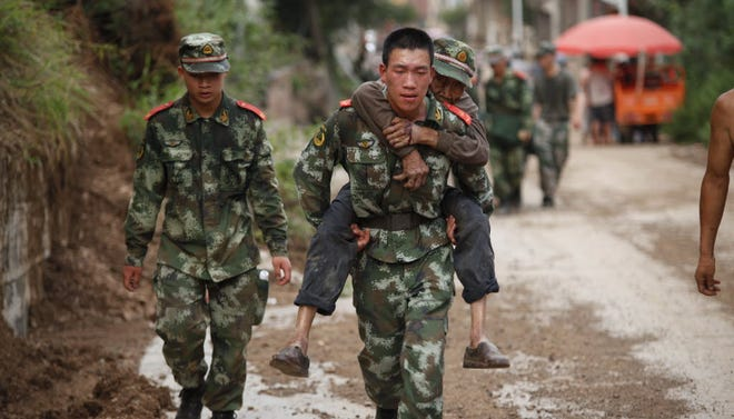 Armed police rescue the wounded after a magnitude-6.5 earthquake on Aug. 3 in Zhaotong, in China's Yunnan province.