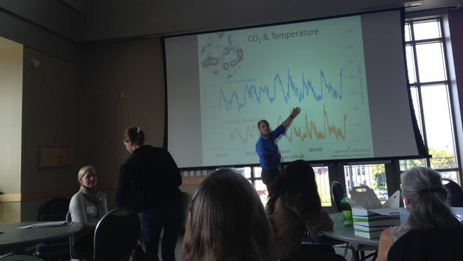 Cameron Wake, a climate scientist from the University of New Hampshire, explains a graph Thursday at an audience at UVM. The chart shows atmospheric carbon dioxide concentrations (top squiggle) and Antarctic temperatures (bottom squiggle) going back 800,000 years. His point was that when CO2 levels were high, so were temperatures, and vice versa.