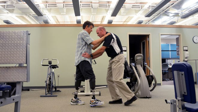 Jeffery Ford works with physical therapist Dick Evans during a session July 28 at University of Iowa Hospitals and Clinics. Ford, a well-known community volunteer, had both legs amputated below the knee and lost large portions of all 10 fingers after a battle with sepsis last year.