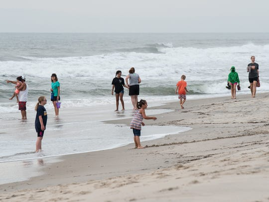 Families gather on the beach just before the start of the Beach Walk at Chincoteague Wildlife Refuge on Monday, July 24, 2017.