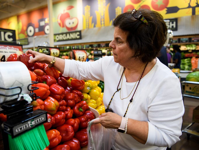 Debbie Lyles picks out peppers at Sprouts Farmers Market