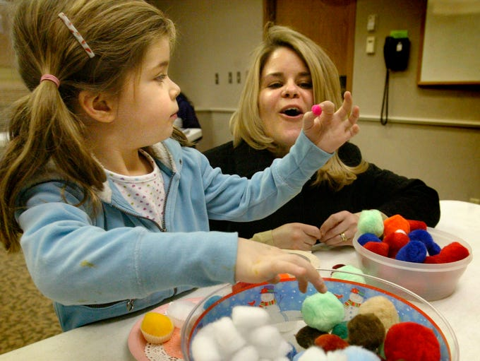 Morgan Betts, 5, adds to her Valentine Day's craft