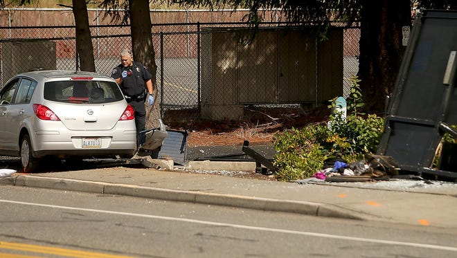 Bremerton Police Officer John Rivera investigates after a vehicle drove into a bus stop Sept. 8 in West Bremerton.